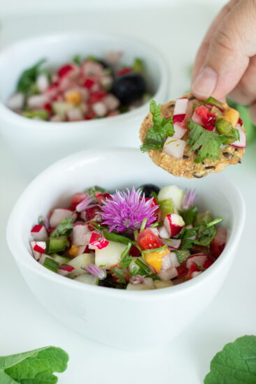 Strawberry radish salsa being scooped on a cracker